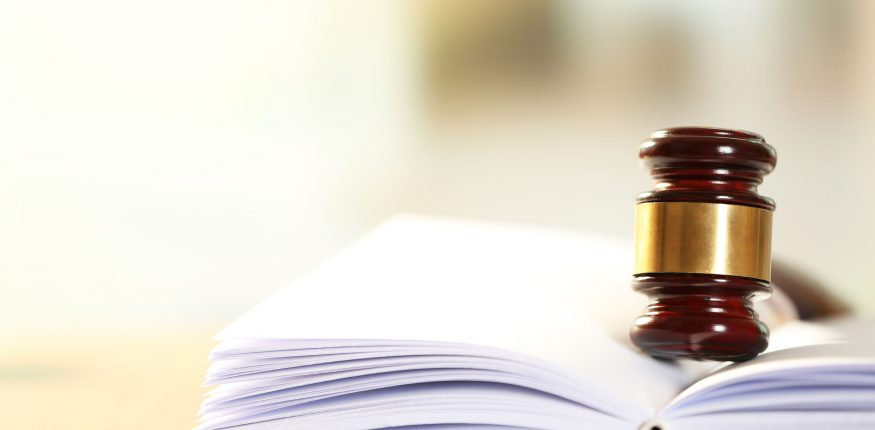 37541054 - wooden judges gavel lying on law book, close up